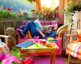 Farbenfrohe Sommerterasse mit Holzmöbeln