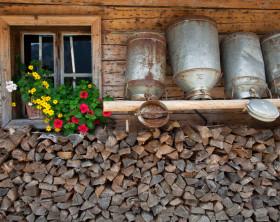 Milchkannen an Hauswand über Holz