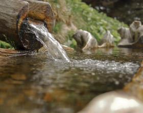 Fließendes Wasser aus einem Holzbrunnen - Nahaufname
