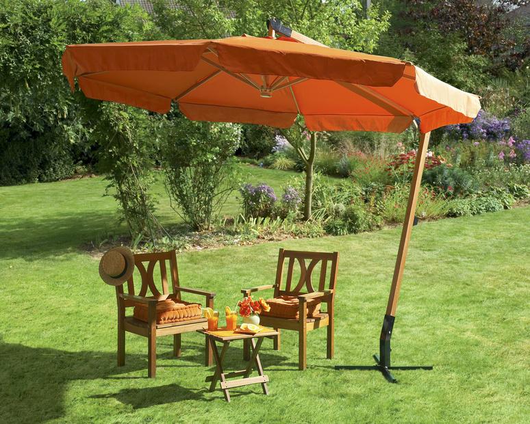 Zwei Stühle unter einem orangefarbenen Ampelschirm