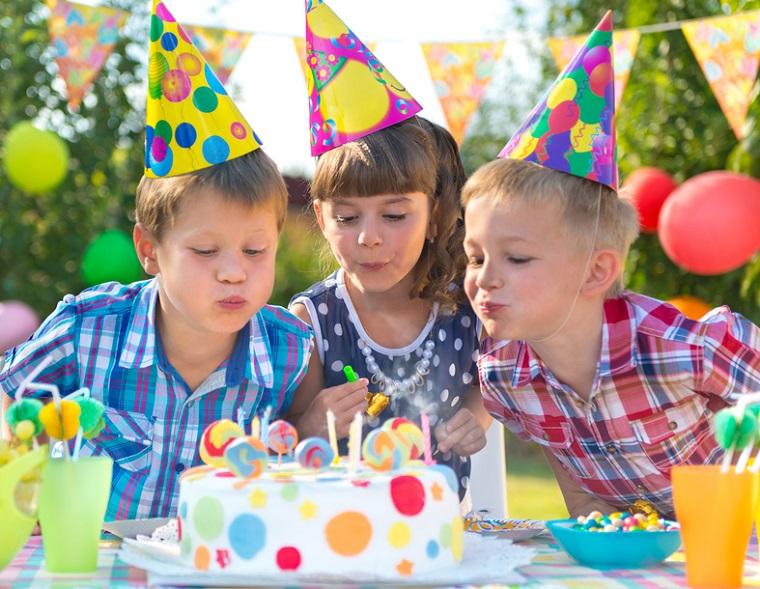 Kindergeburtstag: Kinder pusten Kerzen aus