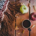 Wolldecke, Äpfel und Becher auf Holztisch
